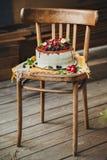 Kaka med bär på träbakgrund Arkivbild