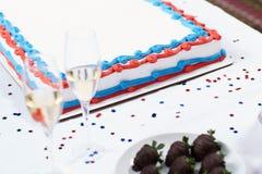 Kaka med exponeringsglas av champagne på tabellen Arkivbilder