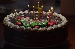 Kaka med färgrika bränningstearinljus i mörker Arkivfoton