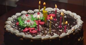 Kaka med färgrika bränningstearinljus i mörker Arkivbilder