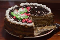 Kaka med färgrika bränningstearinljus i mörker Royaltyfri Bild