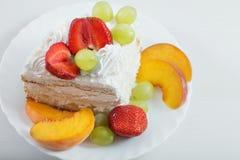 Kaka med frukter på den vita tabellen Arkivfoton
