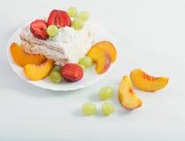 Kaka med frukter på den vita tabellen Royaltyfri Fotografi