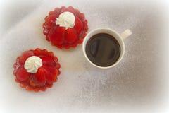 Kaka med jordgubbar och en kopp kaffe Arkivfoto