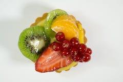Kaka med ny bio frukt, apelsin, kiwi, röd vinbär, jordgubbe, fotosikt uppifrån, vit bakgrund, isolat