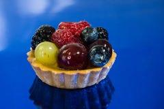 Kaka med nya bio frukter, druvor, hallon, björnbär, foto för sidosikt, blå bakgrund för spegel royaltyfri foto
