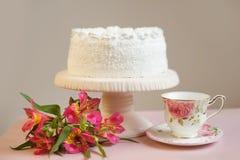 Kaka med piskad kräm på en ställning och livliga ljusa rosa blommor, tetillbehör i bakgrunden Royaltyfri Fotografi