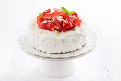 Kaka med piskade kräm och jordgubbar på en ställning Arkivfoton