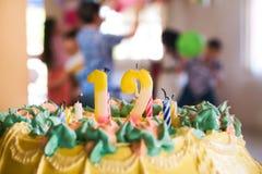 Kaka med 12 stearinljus och barn på födelsedagpartiet Royaltyfria Bilder