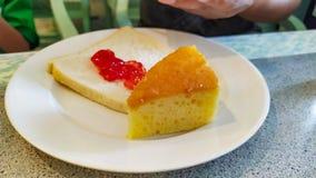 Kaka- och jordgubbedriftstopp på bröd på mycket läcker maträttvit royaltyfri fotografi