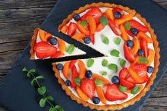 Kaka som överträffas med jordgubbar, aprikors, mintkaramell Fotografering för Bildbyråer