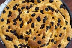 Kaka som göras av bröd med torkade russin i en rund stekhet panna fotografering för bildbyråer