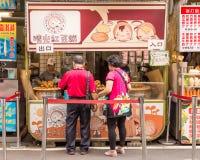 Kakaförsäljare och shoppare för röd böna på Danshui som shoppar område Royaltyfri Foto