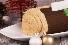 Kakan för chokladyulejournalen med julpynt kasserade på trätabellen Royaltyfria Foton