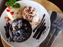 Kakan för muffinchoccolatelava med glass och piskar kräm Arkivfoton