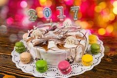 Kakan för nytt år med stearinljus numrerar 2017 på träskrivbordet, brigh Royaltyfri Fotografi