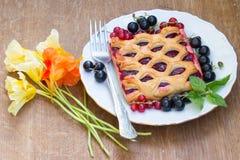Kakan med bärdriftstopp tjänas som med den nya röda och svarta vinbäret Arkivfoto