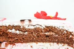 Kakan med scharlakansröda blommor dekoreras foto fotografering för bildbyråer