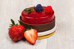 Kakan och jordgubben för chokladglasyrbär på den vita tabellen Royaltyfria Foton