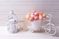 Kakan poppar i dekorativa cykel och stearinljus på vita trälodisar Royaltyfri Bild