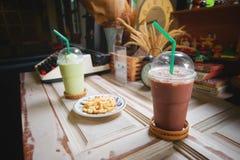 Kakao, choklad och grönt te mjölkar frappe i klart plast- exponeringsglas har grönt sugrör och alfabetkakor på den wood hyllan på royaltyfria bilder