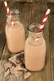 Kakao in den Flaschen auf Holz Lizenzfreies Stockfoto
