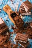 Kakao i sked och choklad med krämig fyllning på blått stiger ombord Royaltyfri Bild