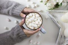Kakao med marshmallower i kvinnlighänder på vit bakgrund Royaltyfria Foton