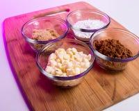 Kakao, pudrat socker och vitchokladchip - baka ingredienser Arkivfoto