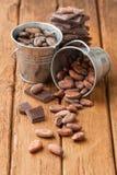 Kakaobohnen in zwei Zinneimern und in der dunklen Schokolade Stockfoto
