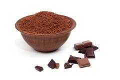 Kakaopulver in einer Lehmhochebene nahe bei Stücken Schokolade Lizenzfreie Stockfotos