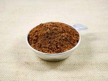 Kakaopulver, i att mäta koppen royaltyfri fotografi