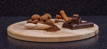 Kakaotryfflar, kakaopulver, choklad och kanelbruna pinnar på en w Fotografering för Bildbyråer