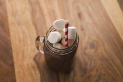 Kakaowy napój w szklanym słoju z rękojeścią na drewno stole Obrazy Stock