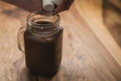Kakaowy napój w szklanym słoju z rękojeścią na drewno stole Obraz Royalty Free