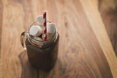 Kakaowy napój w szklanym słoju z rękojeścią na drewno stole Fotografia Stock