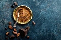 Kakaowy proszek, fasole i ciemni czekoladowi kawałki miażdżący, kulinarny tło obrazy stock