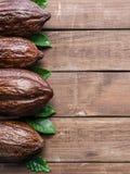 Kakaowy strąk i kakao opuszczamy ustawiony jako część rama na drewnianym tle obraz stock