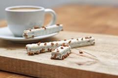 Kakarån i glasyr och kopp kaffe på en trätabell fotografering för bildbyråer