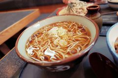 Close up Japanese cusine, hot soba noodles topped with japanese bunching onion in japanese restaurant. Kake Soba, close up Japanese cusine, hot soba noodles royalty free stock photos