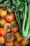 Kaki and celery. Close up on a  of kaki and green celery Stock Photos