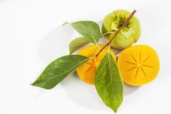 Kaki fruit on white background, halved Stock Photography
