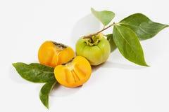 Kaki fruit on white background, halved Royalty Free Stock Photos