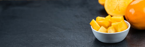 Kaki fruits on a slate slab selective focus Royalty Free Stock Image