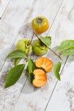 Kaki fruits on white wood, halved Royalty Free Stock Images