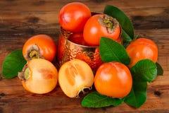 Kaki fruits on wood Oriental East still life Stock Image