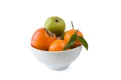 Kaki, mandarine et poire dans un plat Photo stock