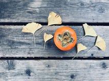 Kaki orange mûr et six feuilles jaunes de ginkgo Image libre de droits