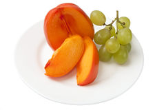Kaki or persimmon fruit and grapes Stock Photos