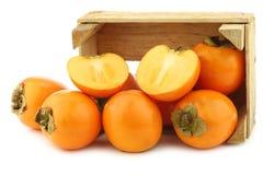 kakifruit in een houten doos Stock Afbeeldingen